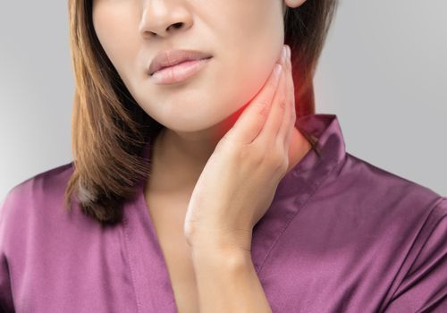 Woman with a sore throat holding her neck, On gray Background