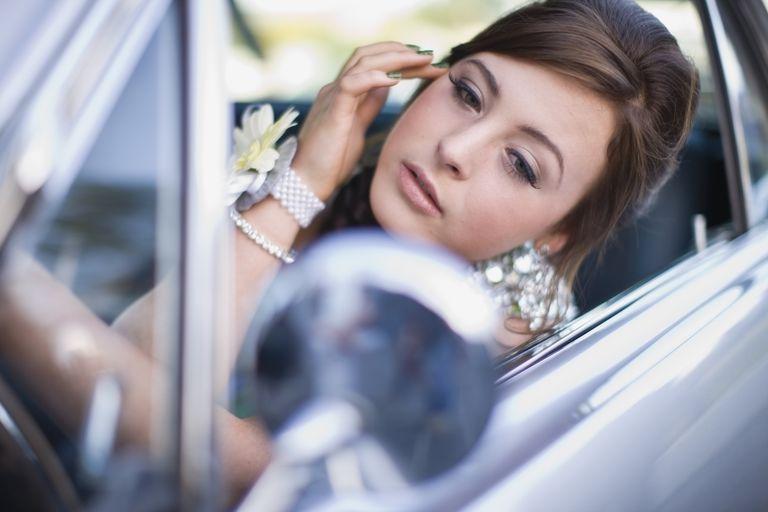 Teenage girl checking makeup in car