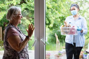 Older woman in her home waving to a young woman in a mask delivering food to her front door.
