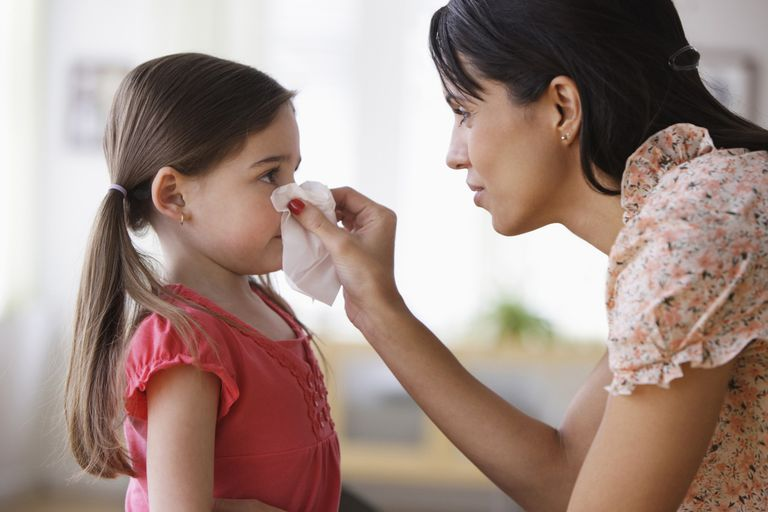 Mother wiping nose of daughter with tissue