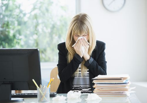 Woman sneezing at her office desk