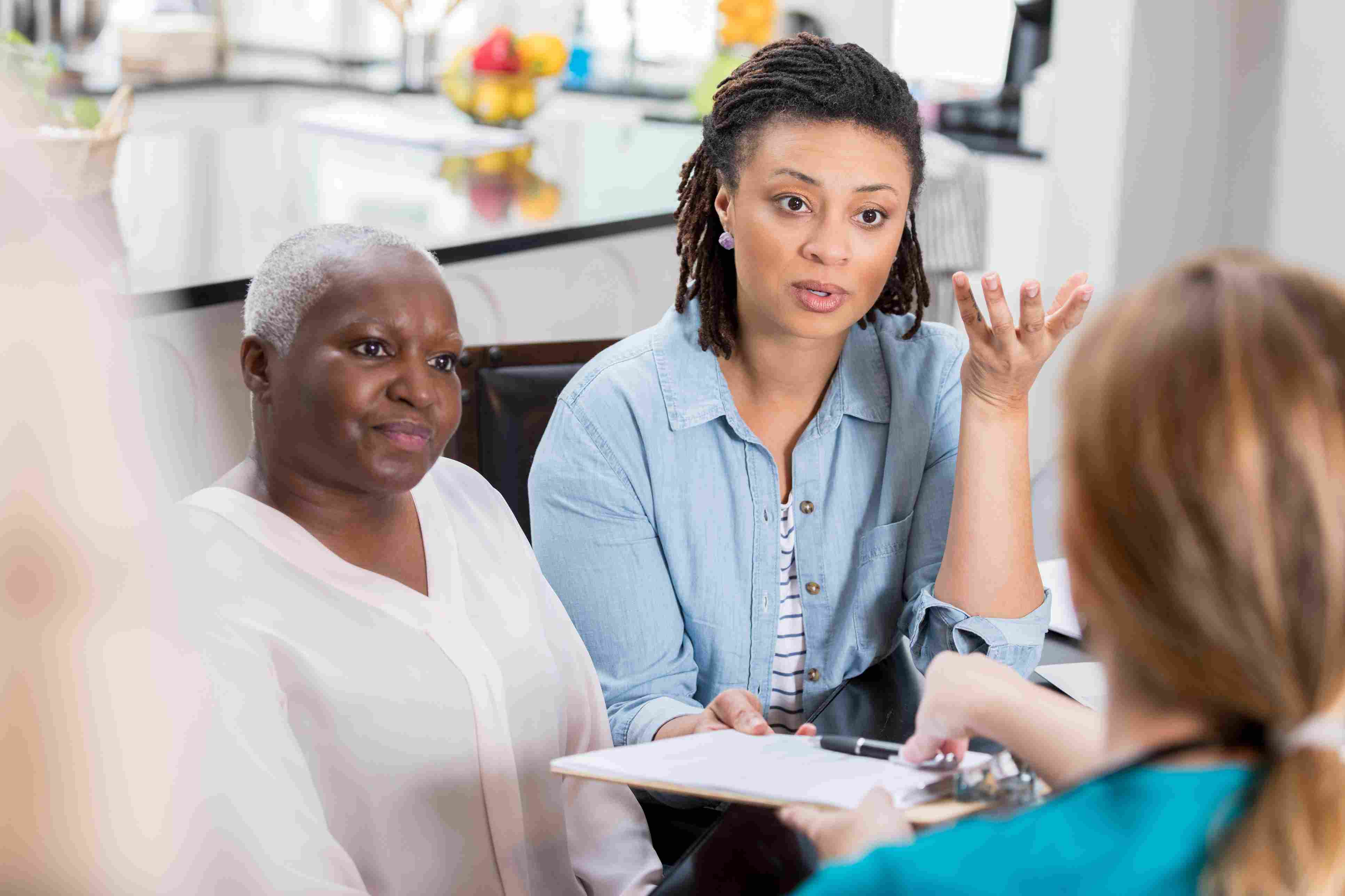 Concerned woman discusses her mother's health with healthcare professional