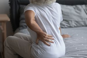 Close up unhealthy mature woman touching back, sitting on bed