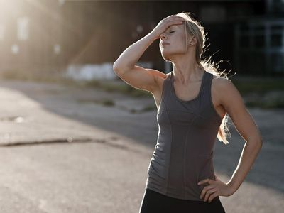 female runner exhausted with hand on head resting on street