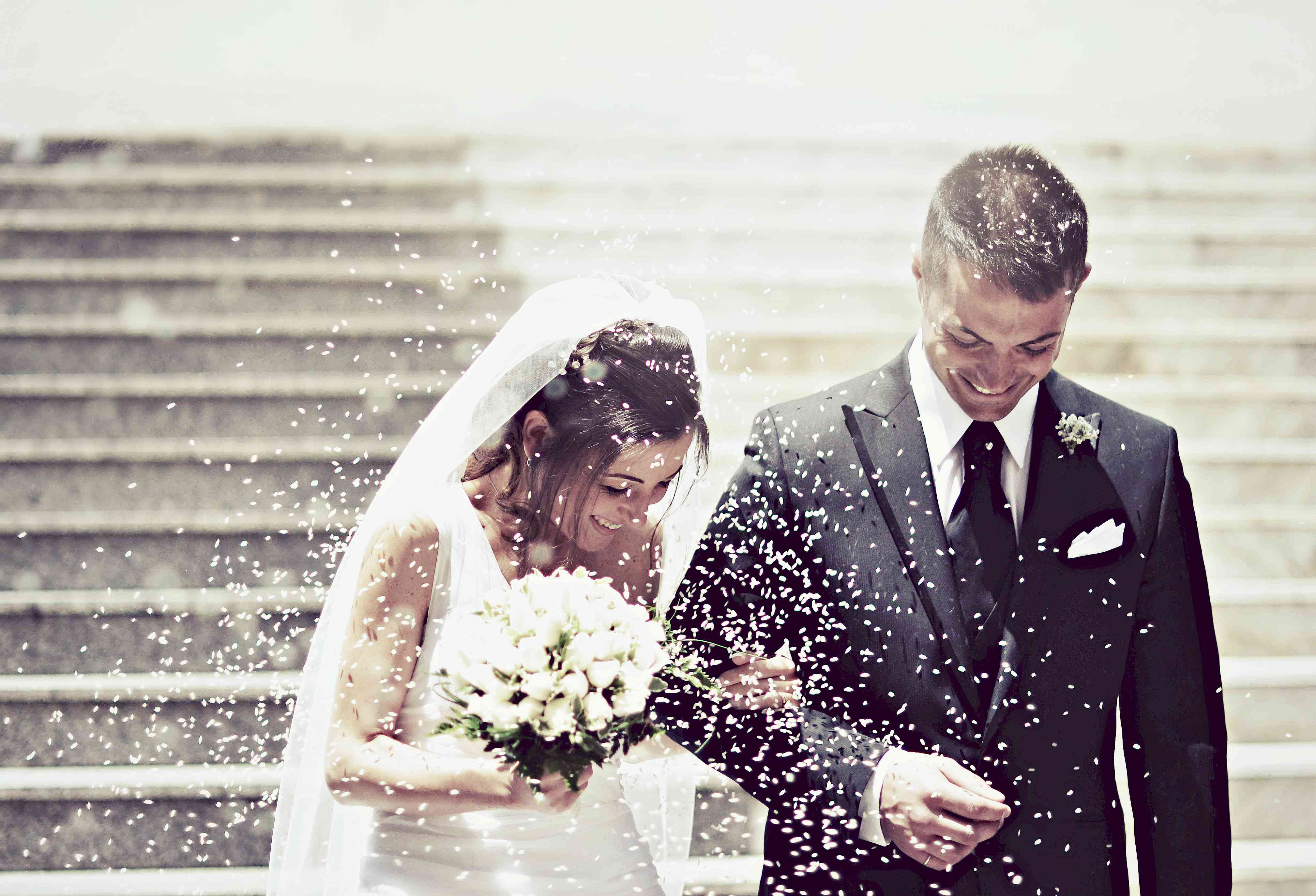 Newlyweds walking outside after ceremony with rice being thrown