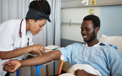 Medical student drawing blood from patient.