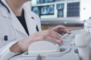 Hispanic doctor using machinery in hospital