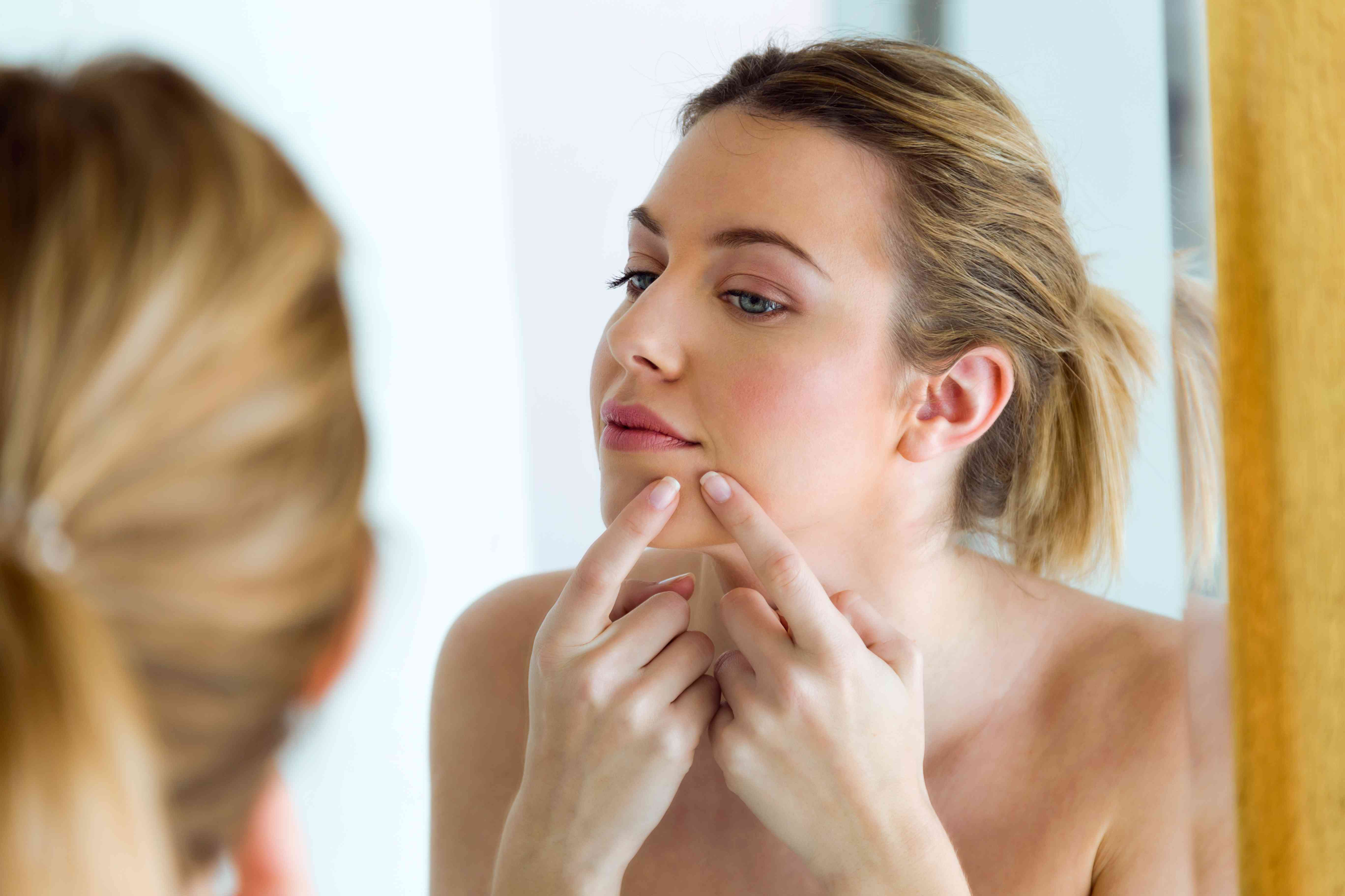 Beautiful young woman removing pimple from her face in a bathroom home.