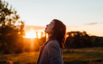 Side portrait of young Asian woman with eyes closed inhaling fresh air, against sunset in the sky.