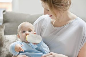 Baby girl feeding on milk with a milk bottle
