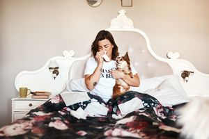 Woman with runny nose holds her dog