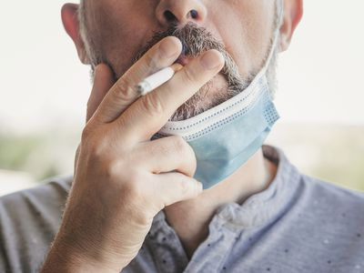 close-up of a man smoking with his mask off
