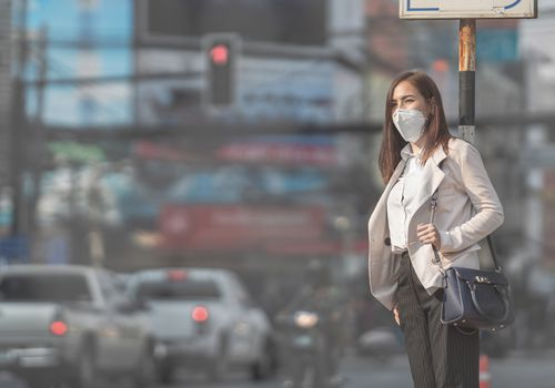 woman standing outside in air pollution, a risk factor for lung cancer