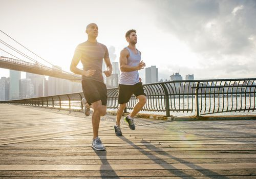 Two male running friends running in front of Brooklyn bridge, New York, USA VIEW DETAILS Two male running friends running in front of Brooklyn bridge, New York, USA