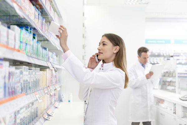 Pharmacist talking on cell phone and removing box from shelf in pharmacy - stock photo.