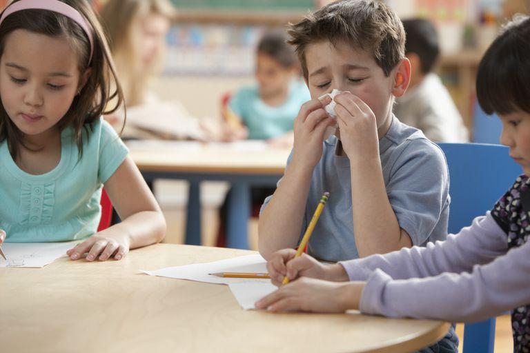 common school illnesses - boy sneezing in classroom