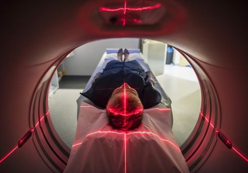Patient lying inside a medical scanner in hospital