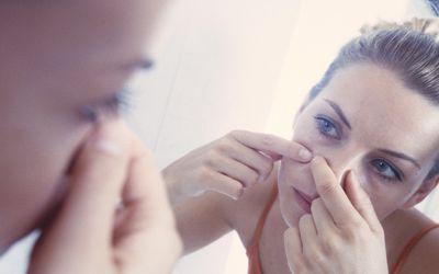 Woman examining acne breakout in the mirror