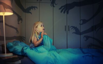 young girl clutching covers in bed, imagining monsters' hands reaching out