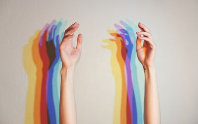 hands with rainbow lights