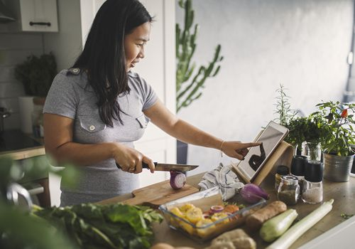 Woman prepping a meal and looking at recipe on tablet