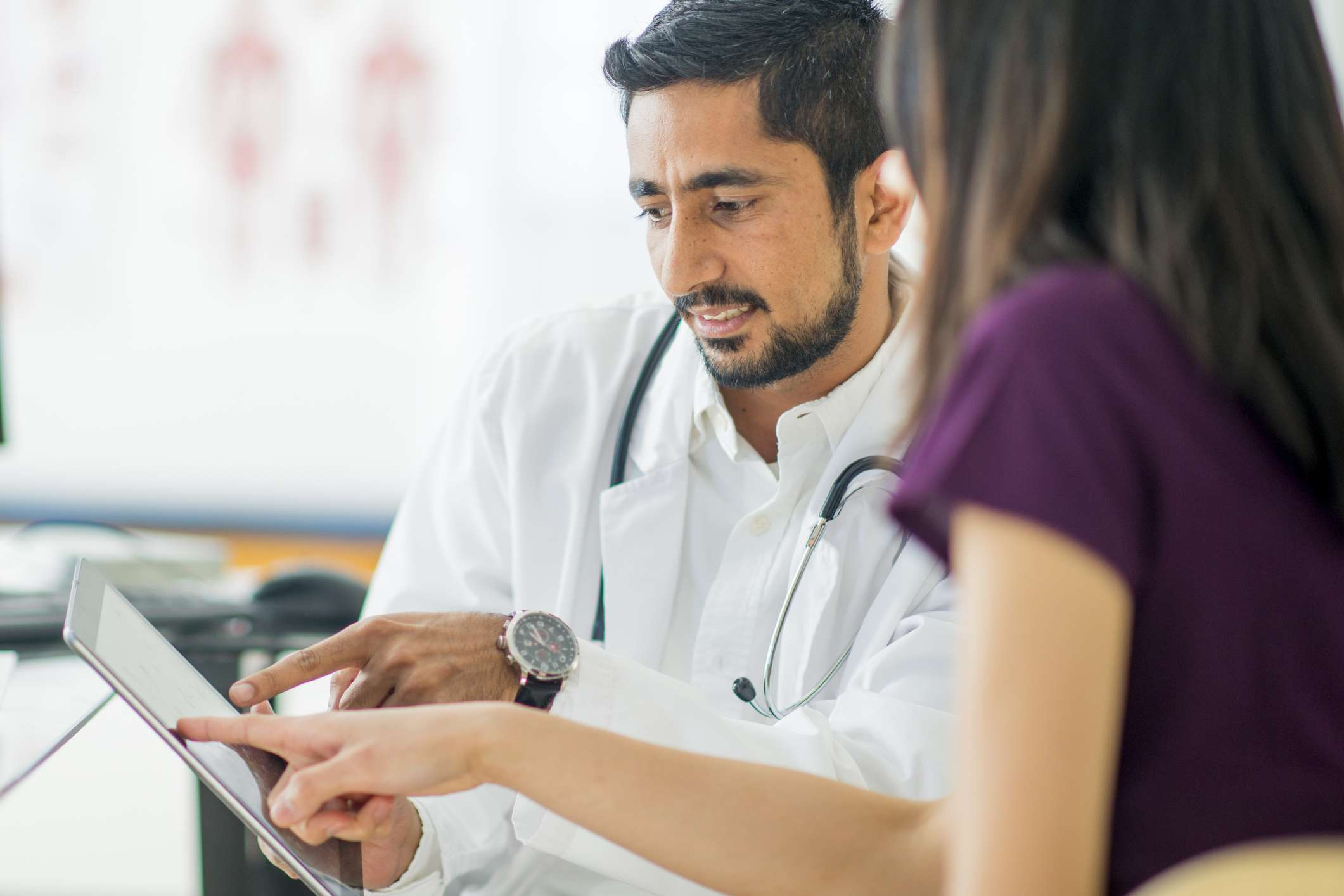 Doctor showing information on a tablet to a patient