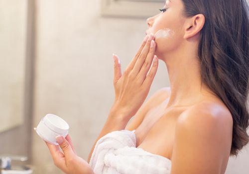 Young woman spreading facial cream in the bathroom