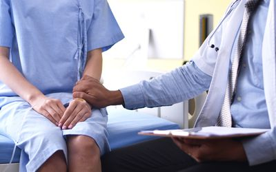 Doctor touching hand of patients to encouragement for the treatment - stock photo