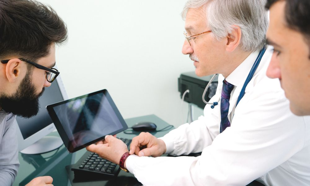 male doctor looking at tablet talking about stage I lung cancer