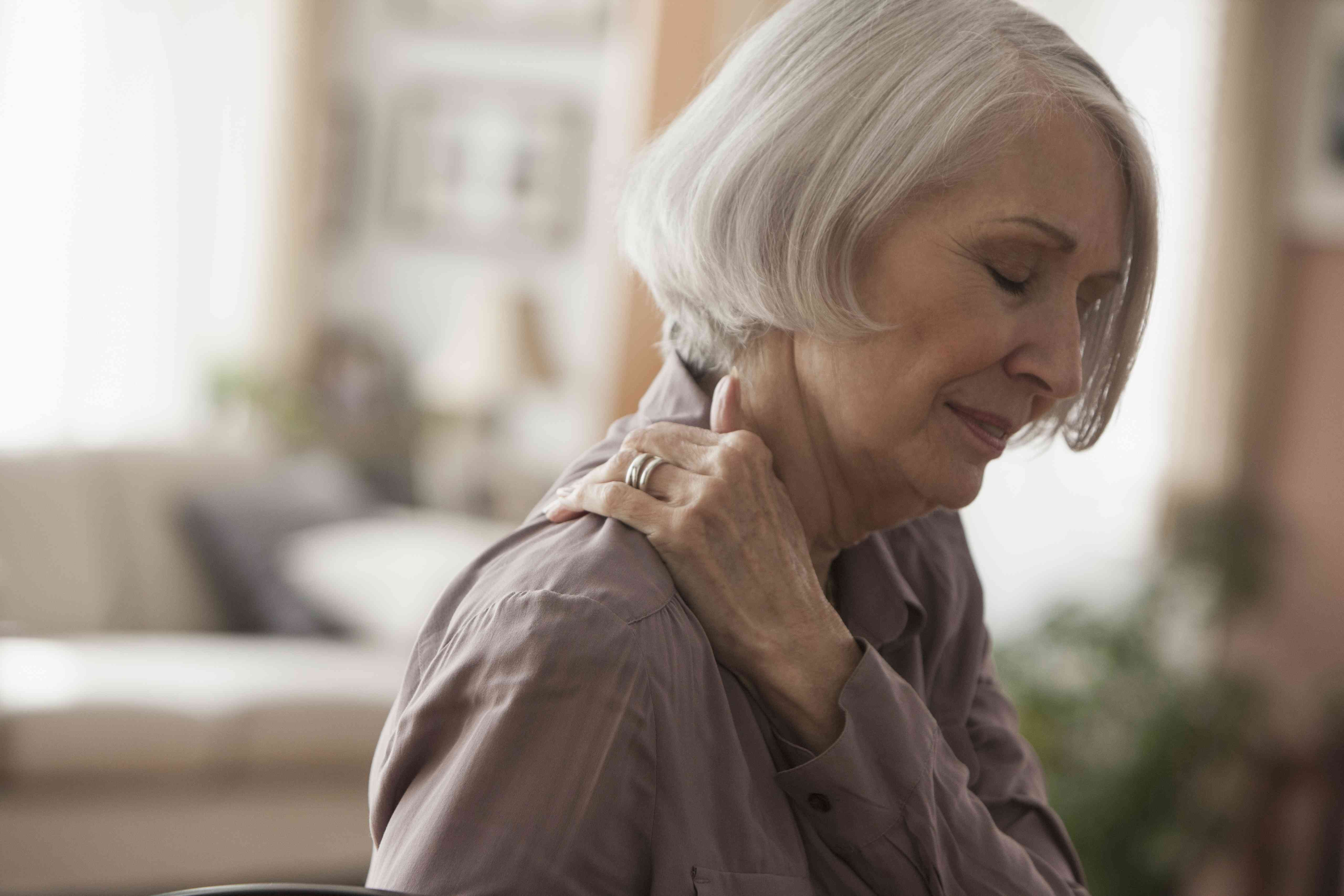 An elderly woman clutches her painful shoulder.