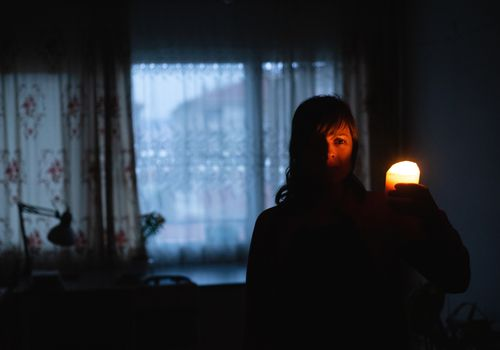 A woman holding a lit candle in the middle of a dark room; only half her face is in the light.