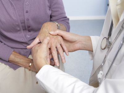 General practitioner examining patient and hand for signs of rheumatoid arthritis