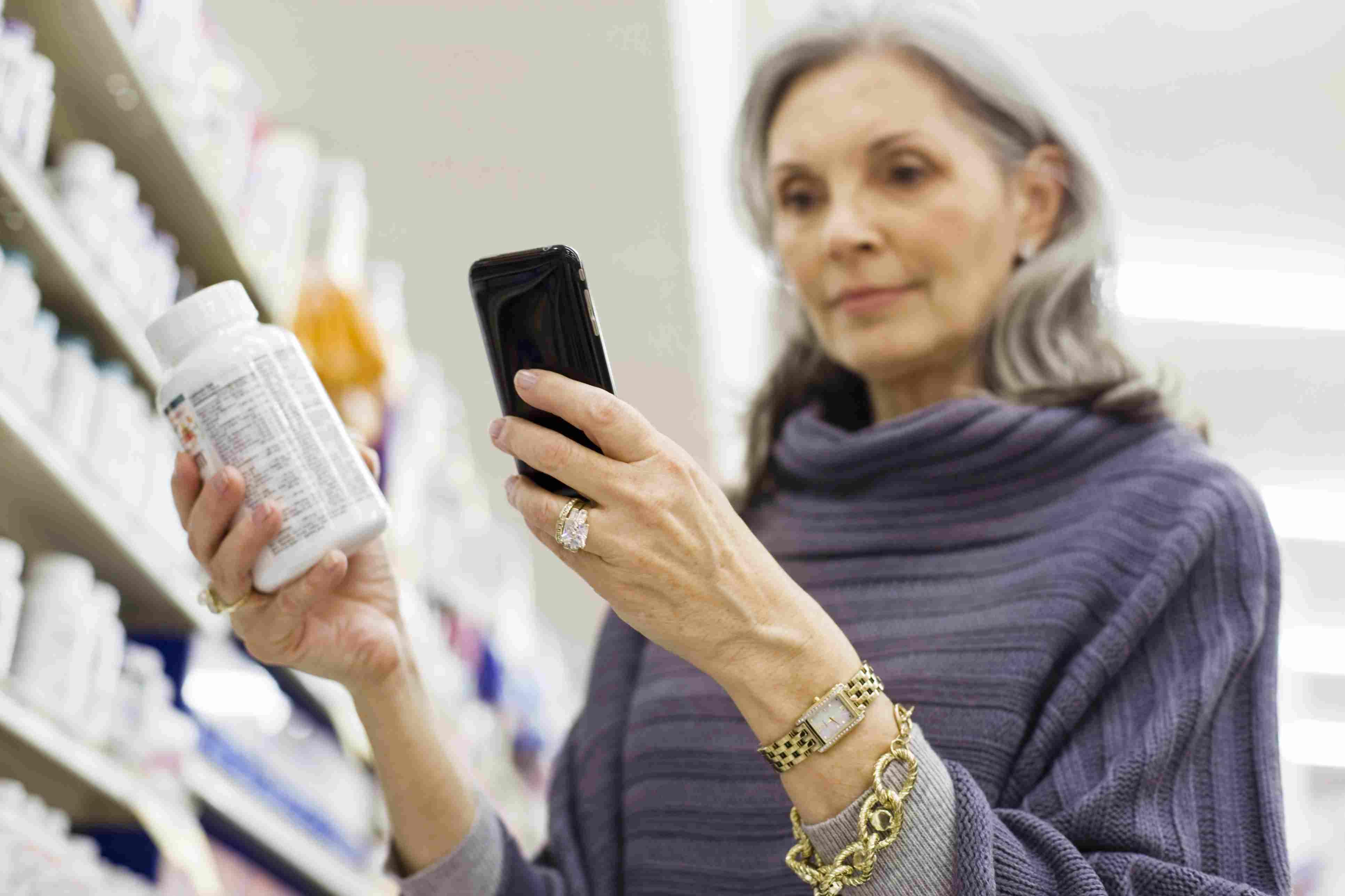 Senior woman reading medicine bottle