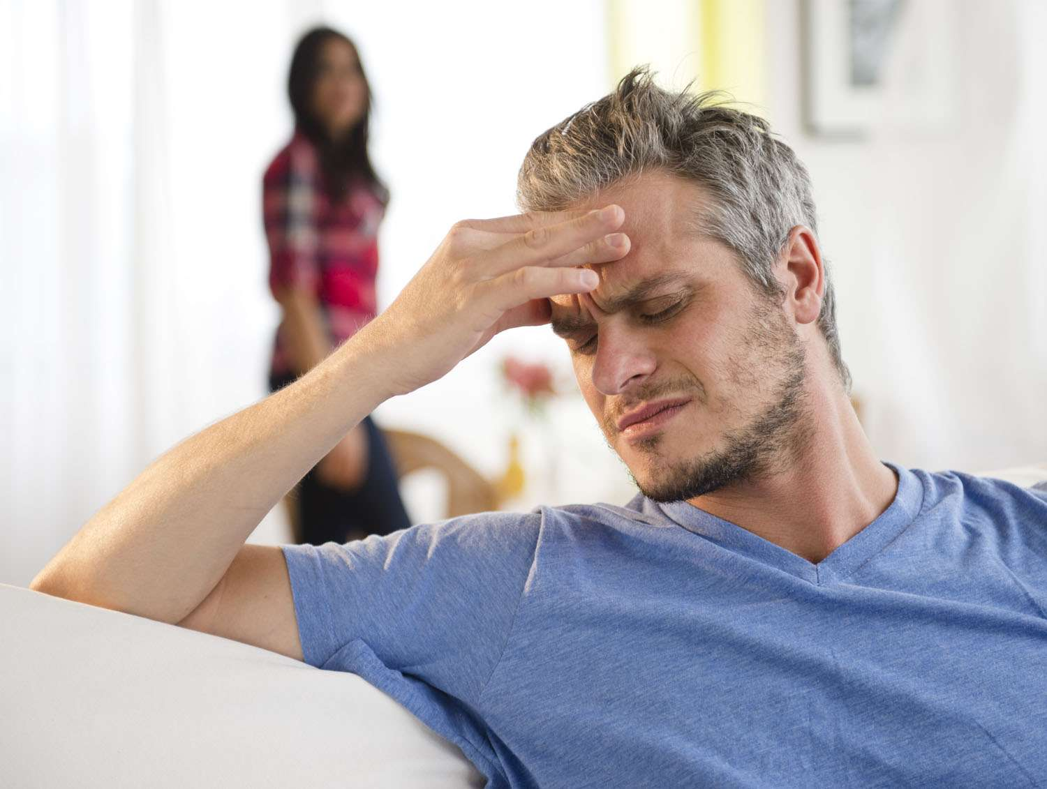 Man sitting on couch with headache