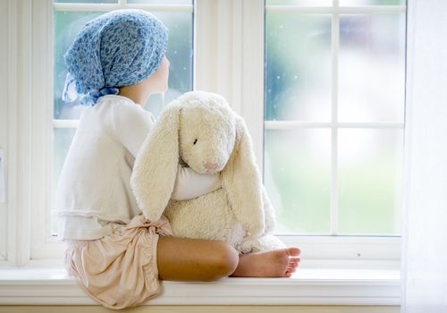 A young cancer patient looking out the window