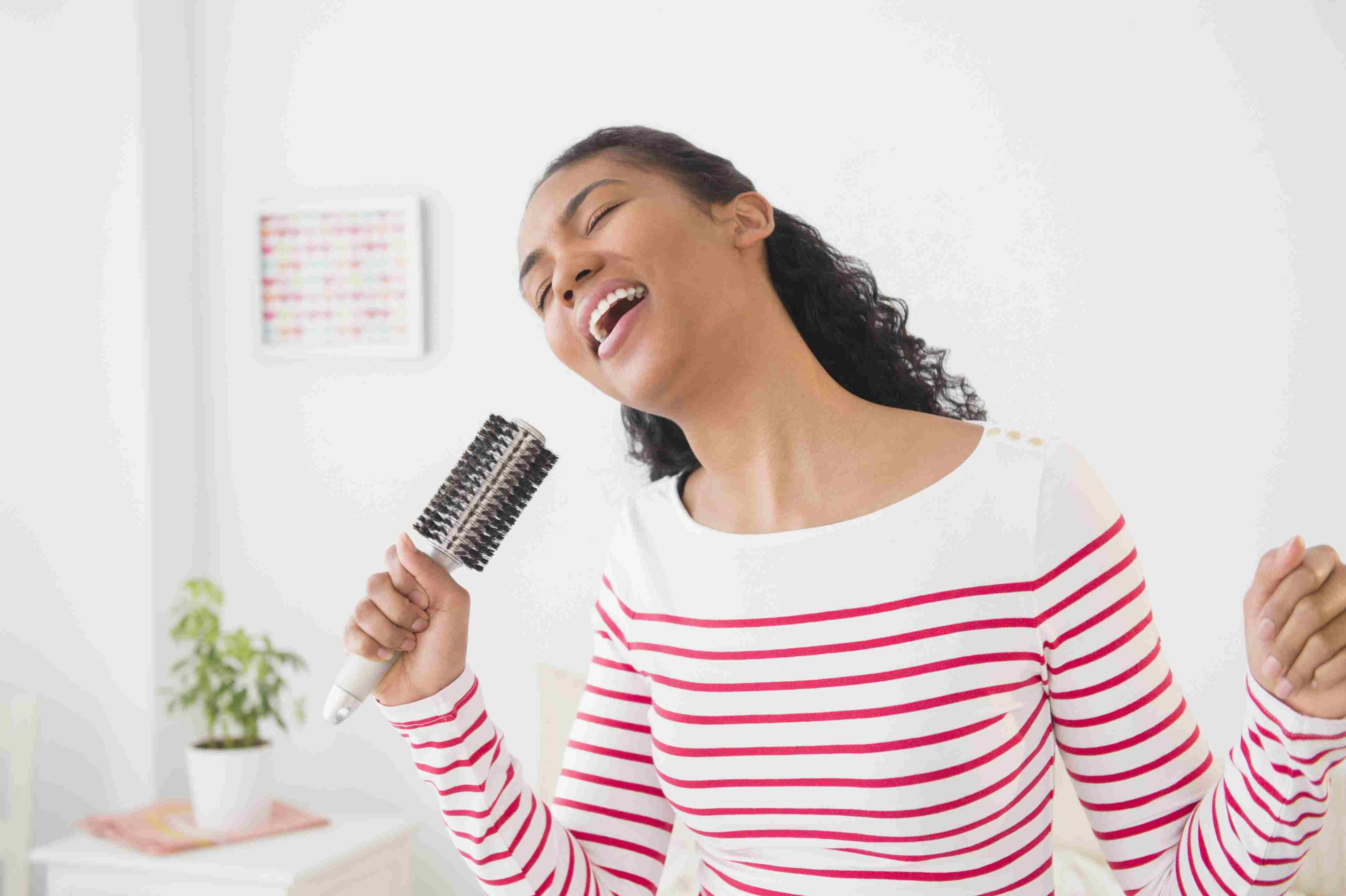 Girl singing and using a hairbrush as a microphone