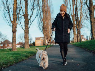 Woman walking her dog outside.
