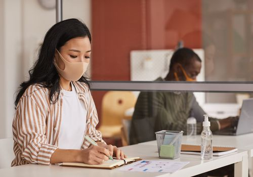 Young Asian woman wearing a face mask working at a desk.