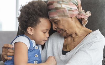A black woman with cancer is wearing a scarf on her head. She is sitting in a lounge chair with her young granddaughter. The two are embracing and their foreheads are touching. They have somber and thoughtful expressions.
