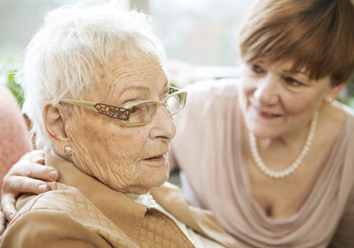 Woman talking to her mother with hr arm around her