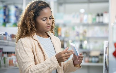 Woman holding contraceptive pills at pharmacy store