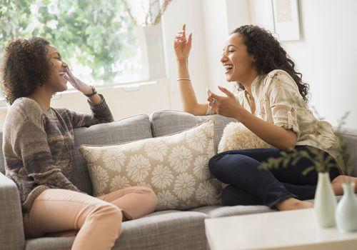 Two Black women laughing and sitting on a couch together at home.