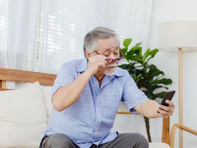 Asian senior fatigue man taking off glasses during using smartphone