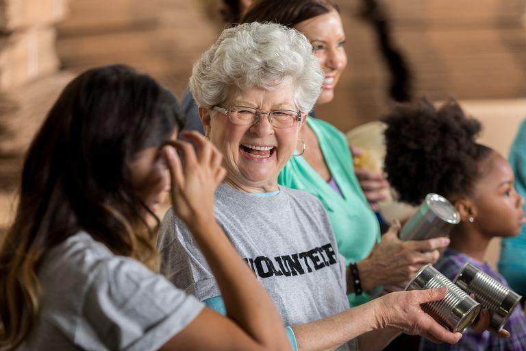 Laughing senior woman wearing a volunteer shirt at a food drive