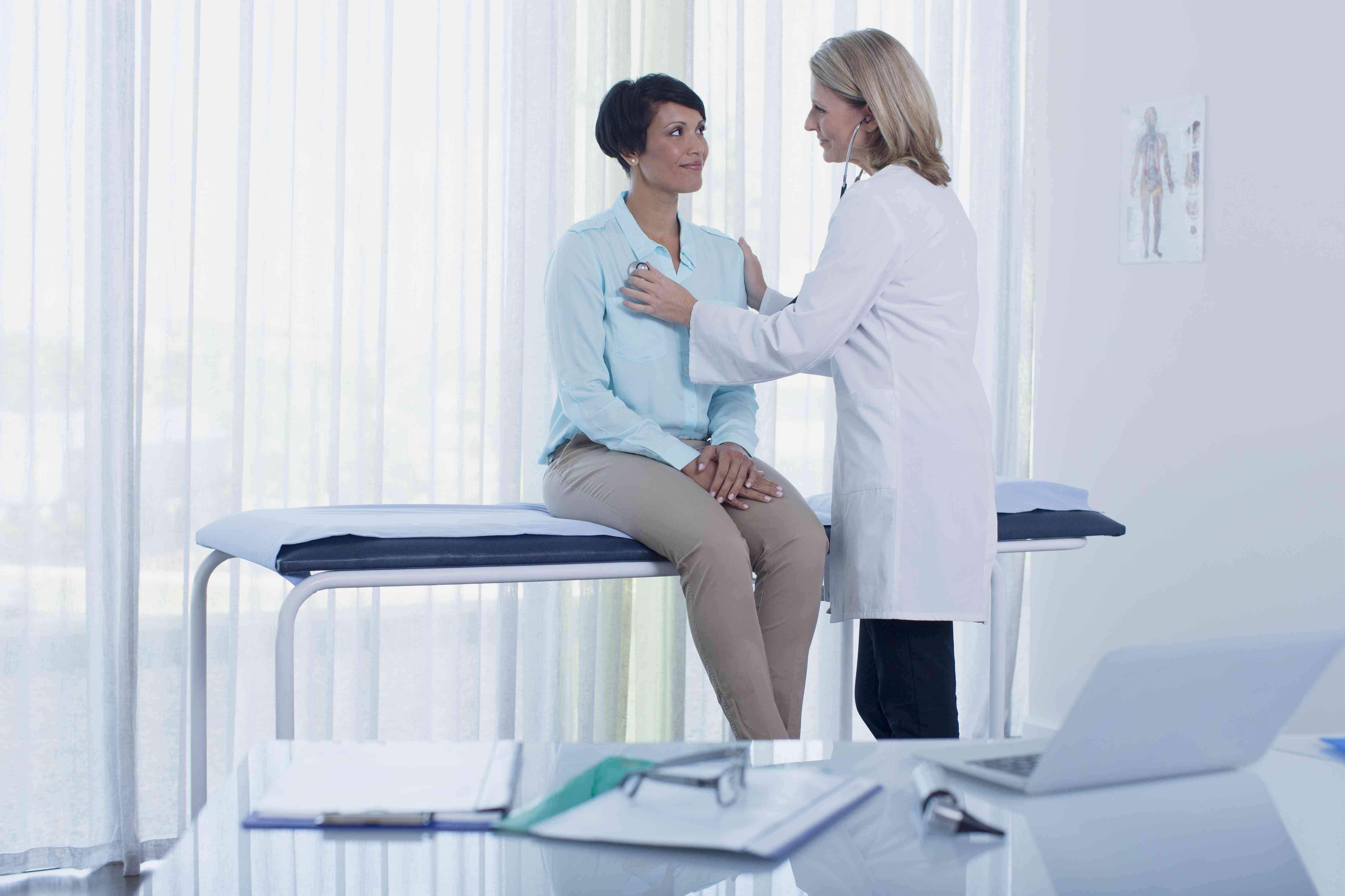 Female doctor examining her patient with stethoscope in office, desk with laptop in foreground