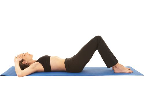 A woman performs the pelvic tilt exercise in hooklying.