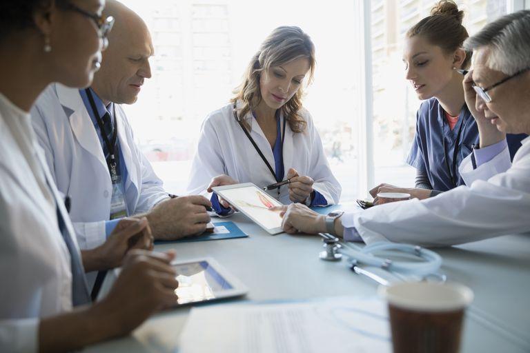 Doctors using digital tablet in meeting