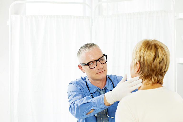 Mature Woman at doctors office. Doctor is doing an external gland exam, touching her glands with hands, using latex gloves.