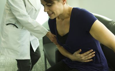Doctor assisting patient with severe abdominal pain