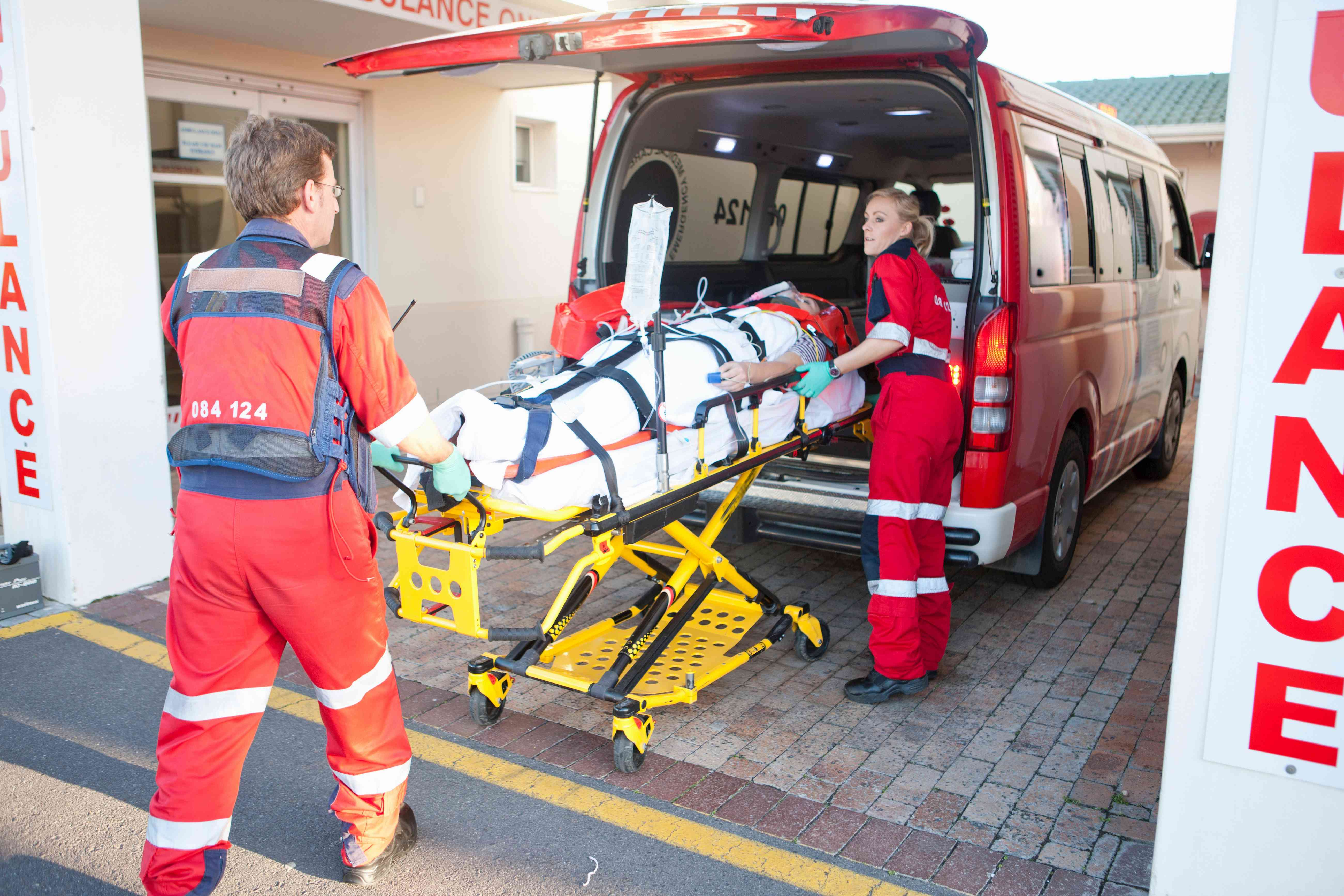 Paramedics lifting a patient from an ambulance
